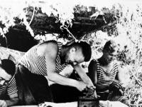 Разведчики 322 батареи В.В. Фомин (пишет письмо), Н.К. Алейников (гладит белье) и П.В. Кундуй (шьет).  Россия, Краснодарский край. Лето 1943 г.  Фот. Н. М. Аснина.